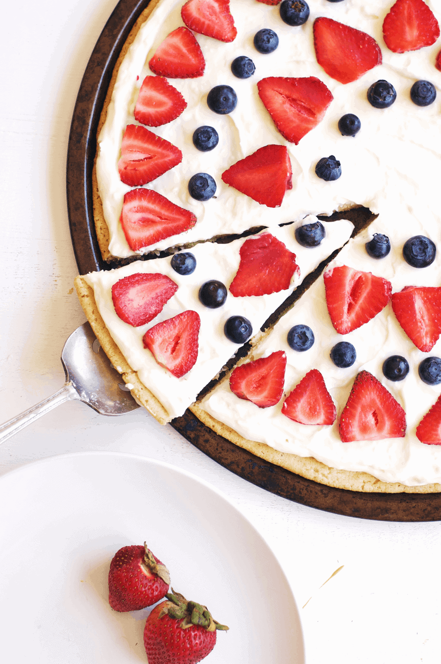 This 4th of July berry dessert pizza needs to be at the top of your list of festive foods to make! The combination of juicy, sweet berries and cream cheese icing spread on a sugar cookie crust is absolutely delicious. You'll definitely be going back for seconds, maybe even thirds! || The Butter Half #easydessert #fruitpizza #summerrecipes #thebutterhalf