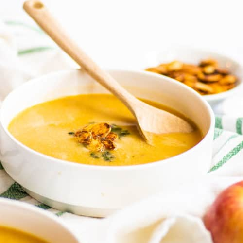 up close shot of yellow butternut squash soup with down spoon and pumpkin seeds on top