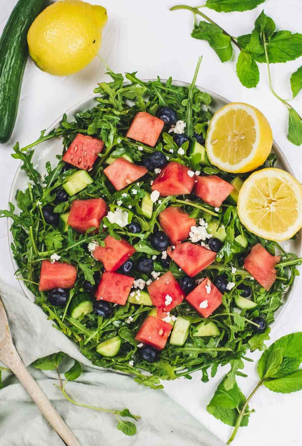 Overhead shot of plate of watermelon and arugula salad with lemons