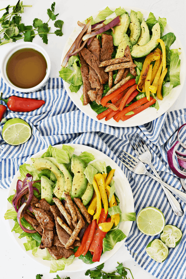 Overhead shot of two white plates steak, avocados, peppers, and salad on white and blue napkin.