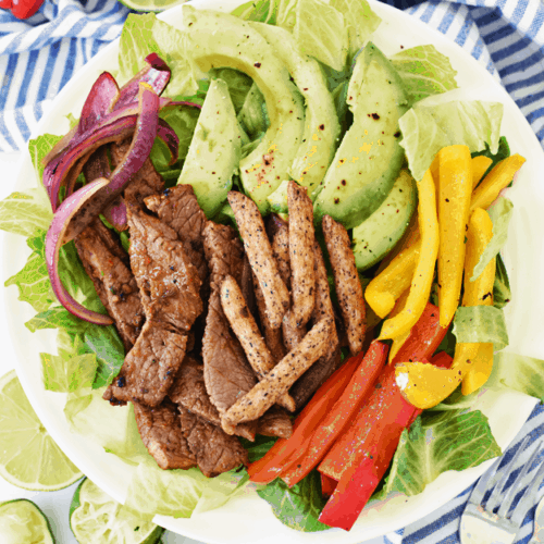 Overhead shot of large plate of steak, avocado, peppers, and onion on white and blue napkin.