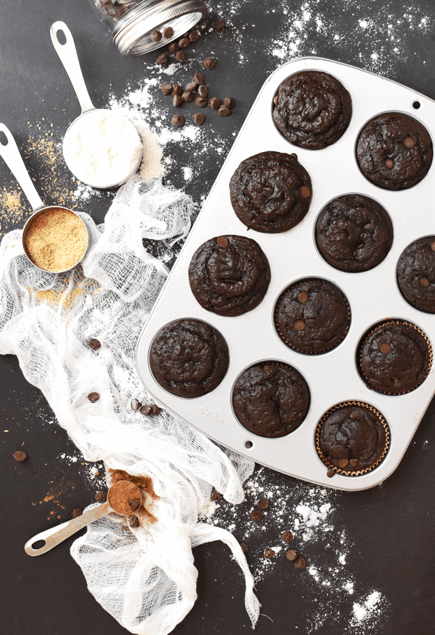 Overhead shot of chocolate muffins in a muffin tin with sugar and measuring cups.