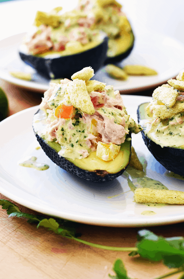 These tuna stuffed avocados with cilantro lime dressing take only 15 minutes to make and taste incredibly fresh and satisfying. They are pocket-friendly, too.  All you need are five wholesome ingredients, plus the dressing. The cilantro lime dressing is fresh, and has a tart and delicious flavor that pairs well with many recipes. Make them for a healthy dinner or lunch that is simple and nourishing. || The Butter Half #avocado #easylunch #dinner #easyrecipe #lunchideas #thebutterhalf