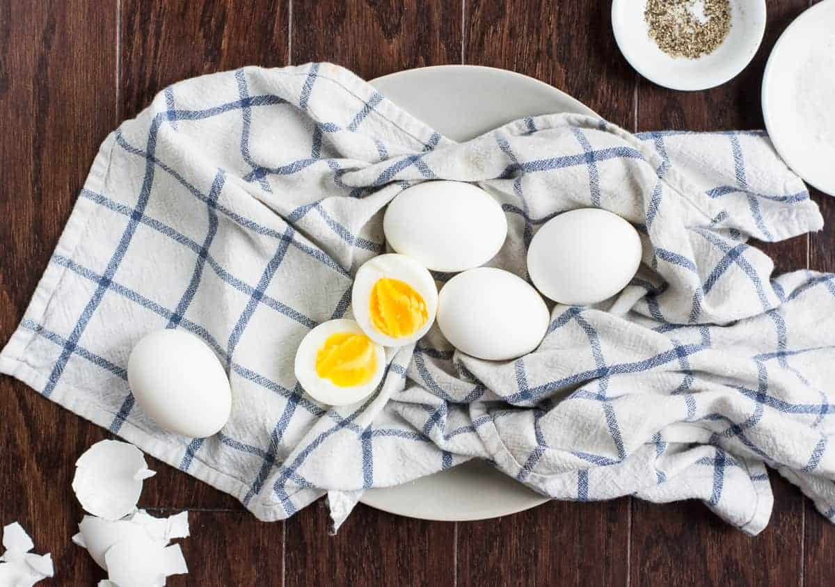 Overhead shot of peeled hardboiled eggs on blue and white kitchen towel