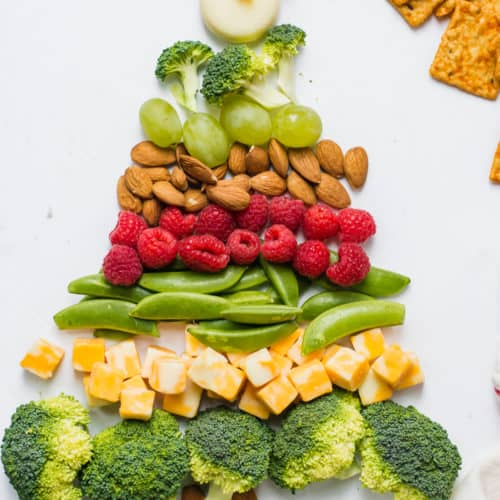 Broccoli, cheese, nuts, grapes, and berries in shape of Christmas tree