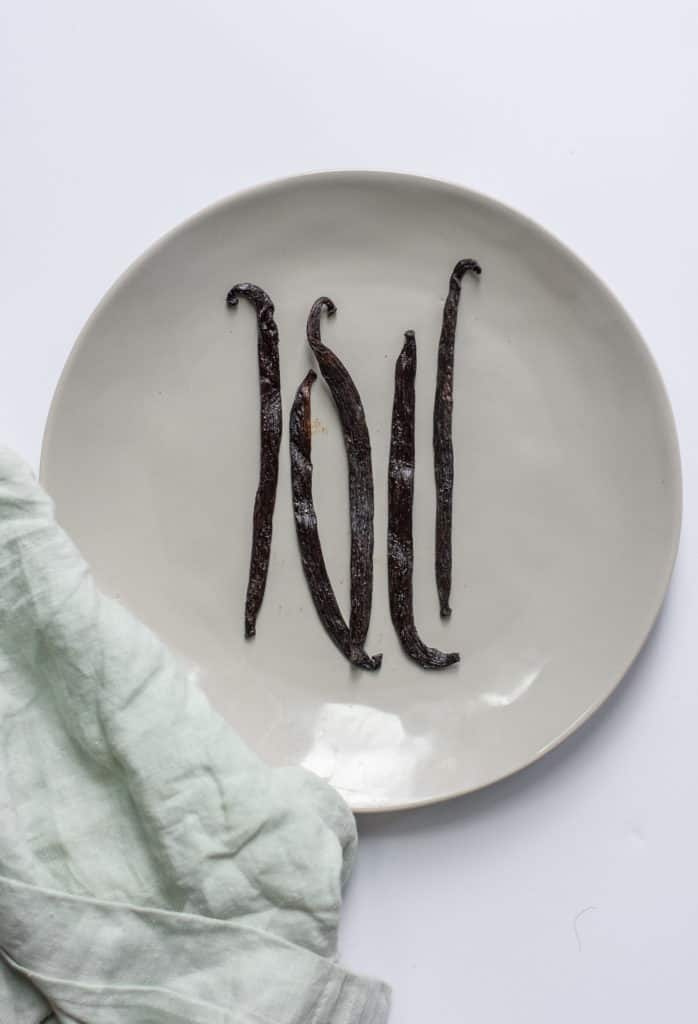 Vanilla bean pods on white plate