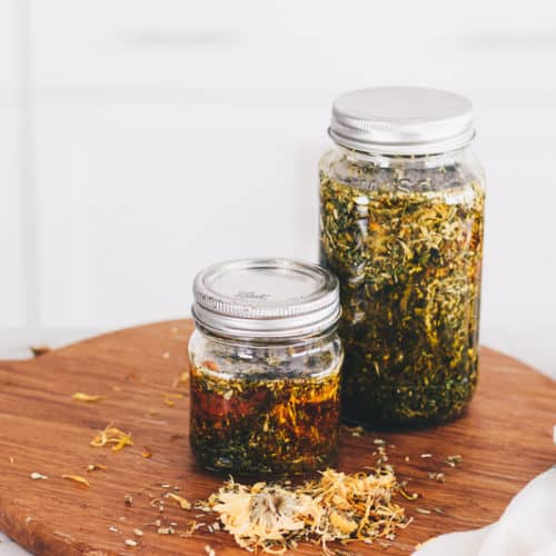 Herb infused oils in two mason jars