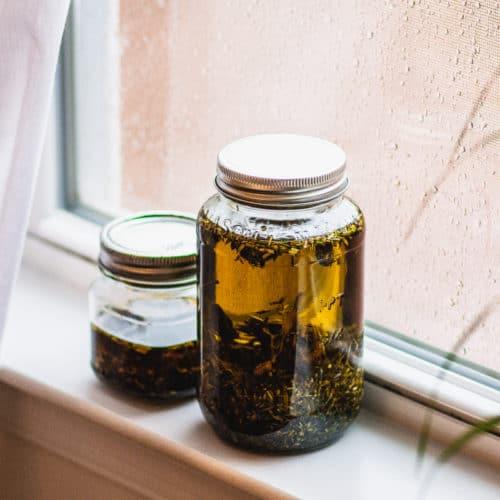 Jars of herb infused oils sitting in windowsill