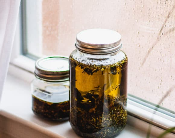 Jars of herb infused oils sitting in windowsill
