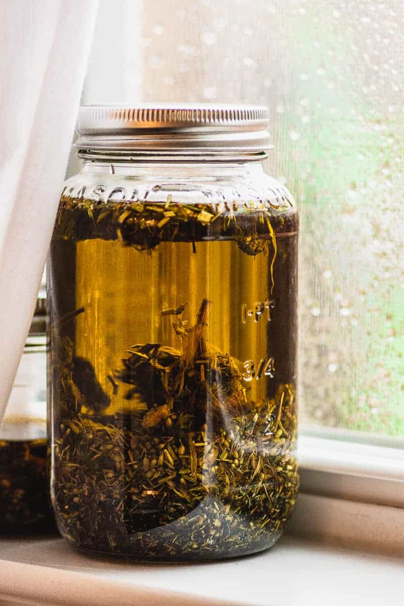 Making Herb Infused Oils is an easy way to enhance your health and cooking. Learn how to make herbal oils with dried herbs and create your own skin care creams, salves, and serums. #herbs #infusedoils #naturalskincare #thebutterhalf