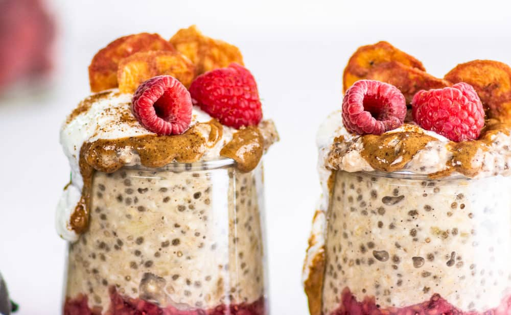 two glass jars with overnight oats, red jam, and raspberries