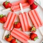 Overhead shot of strawberry popsicles on great plate with strawberries around it