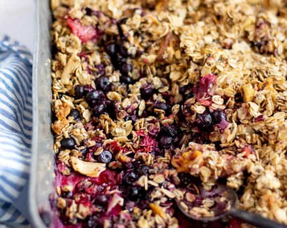 angled shot of finished berry crisp in metal baking pan