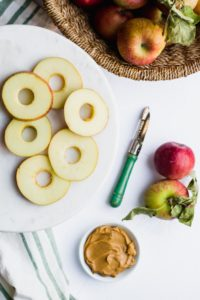 sliced apples on a marble platter with corer and apples on side
