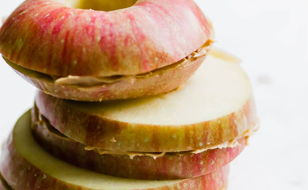 stack of three apple and peanut butter sandwiches