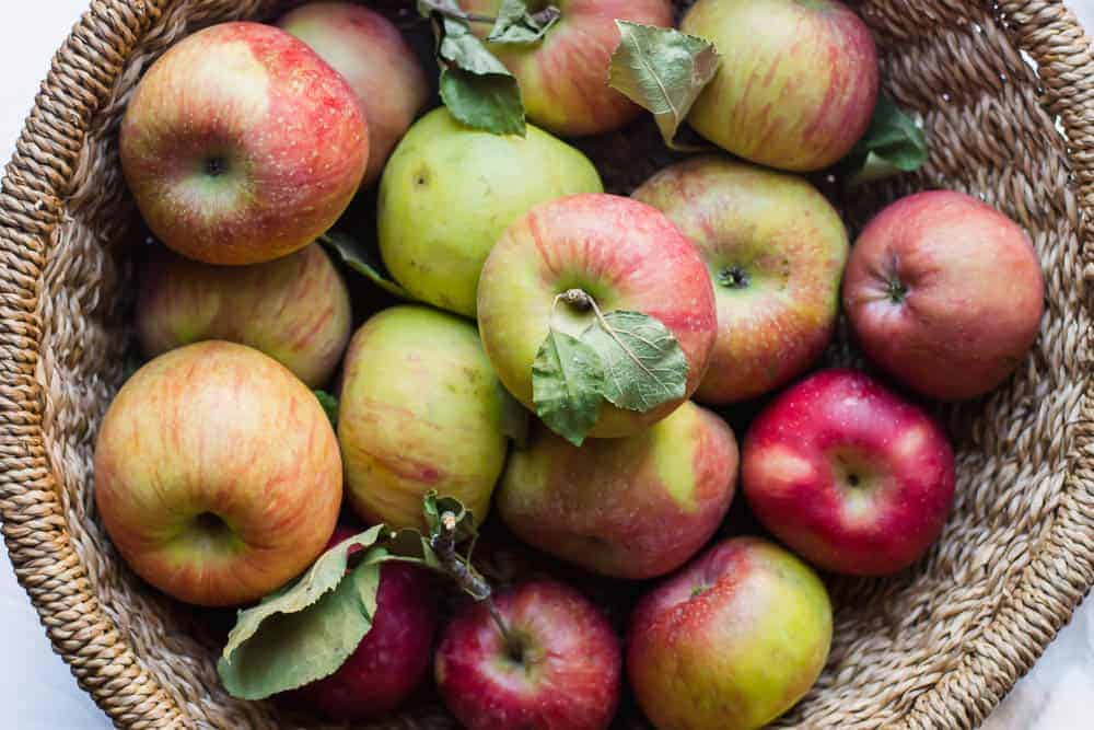 overhead shot of red and green apples in a brown basket