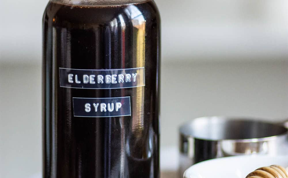 Labeled bottle of elderberry syrup on marble stand